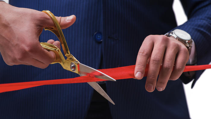 A close up of a man wearing a suit cutting red tape with scissors.
