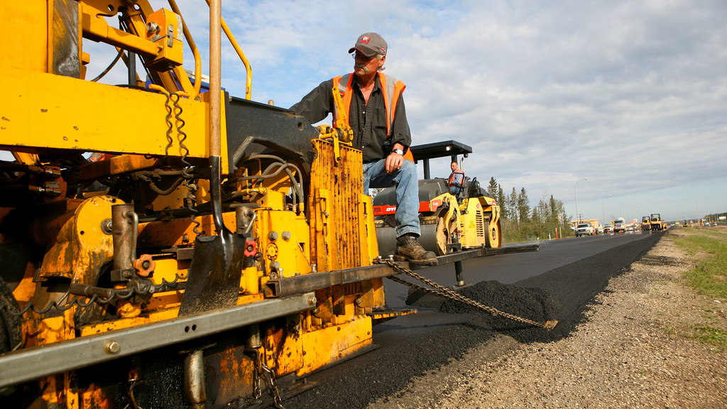 Man operates heavy machinery to construct a new highway