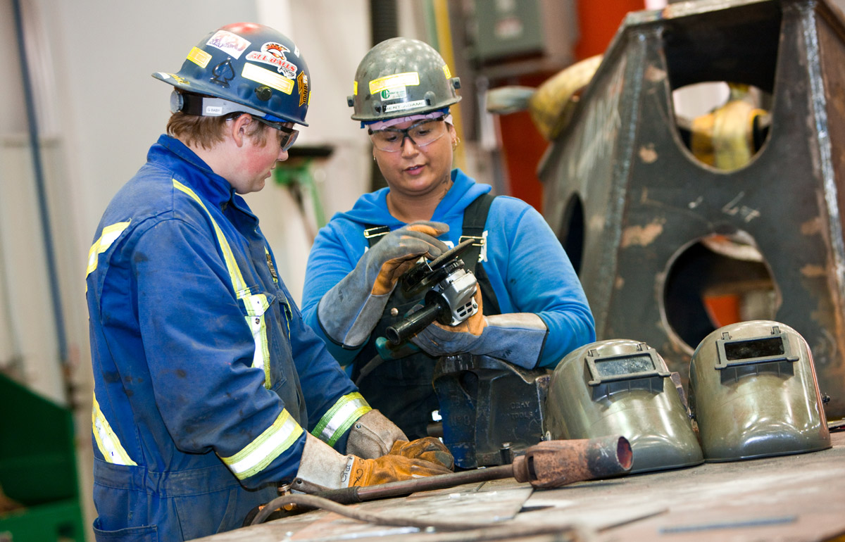 Two young tradespeople work on a welding project