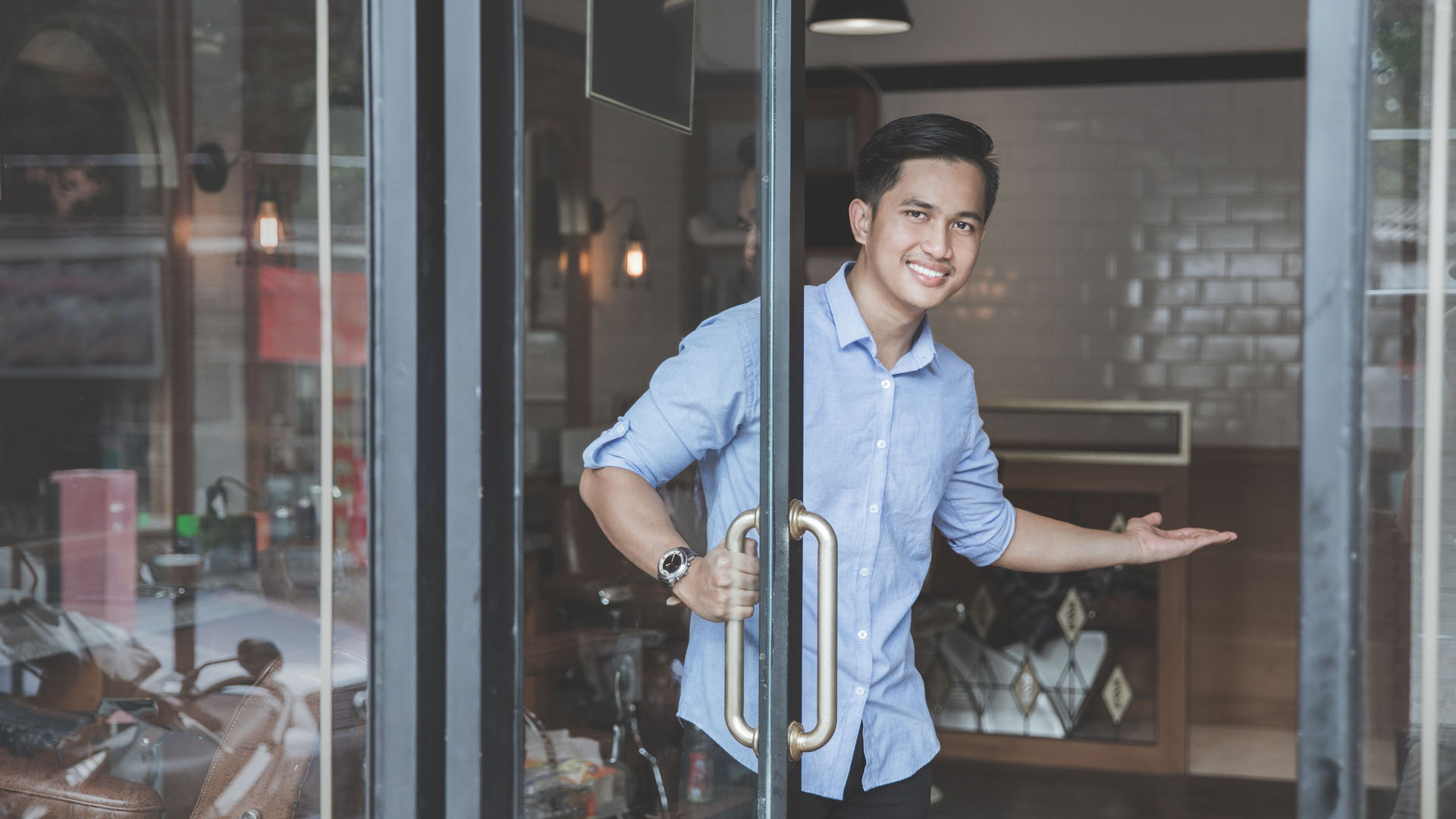 A small business owner holds the door open