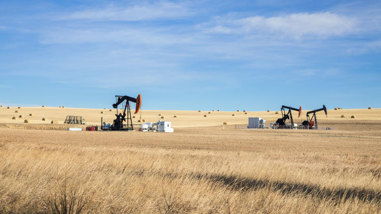Image of 3 oil wells in a wheat field.