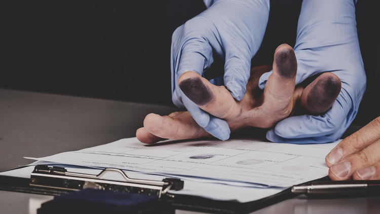 Close up image of hands getting fingerprinted