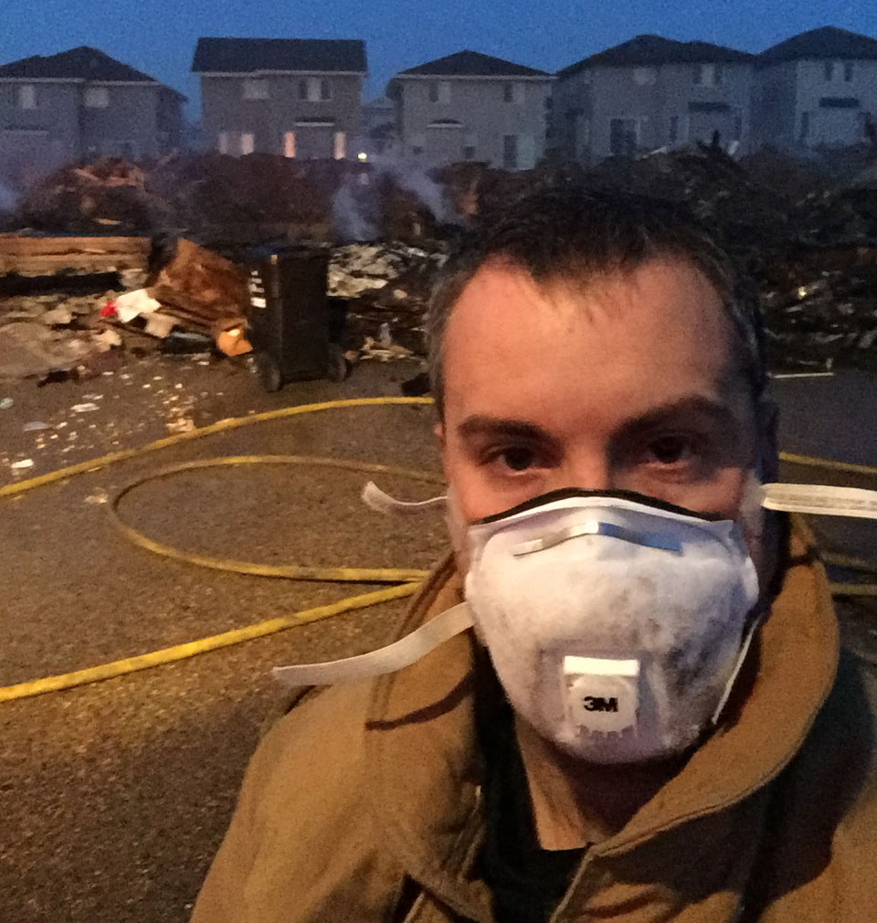 A man with a dust mask with smouldering debris from a neighbourhood behind him.