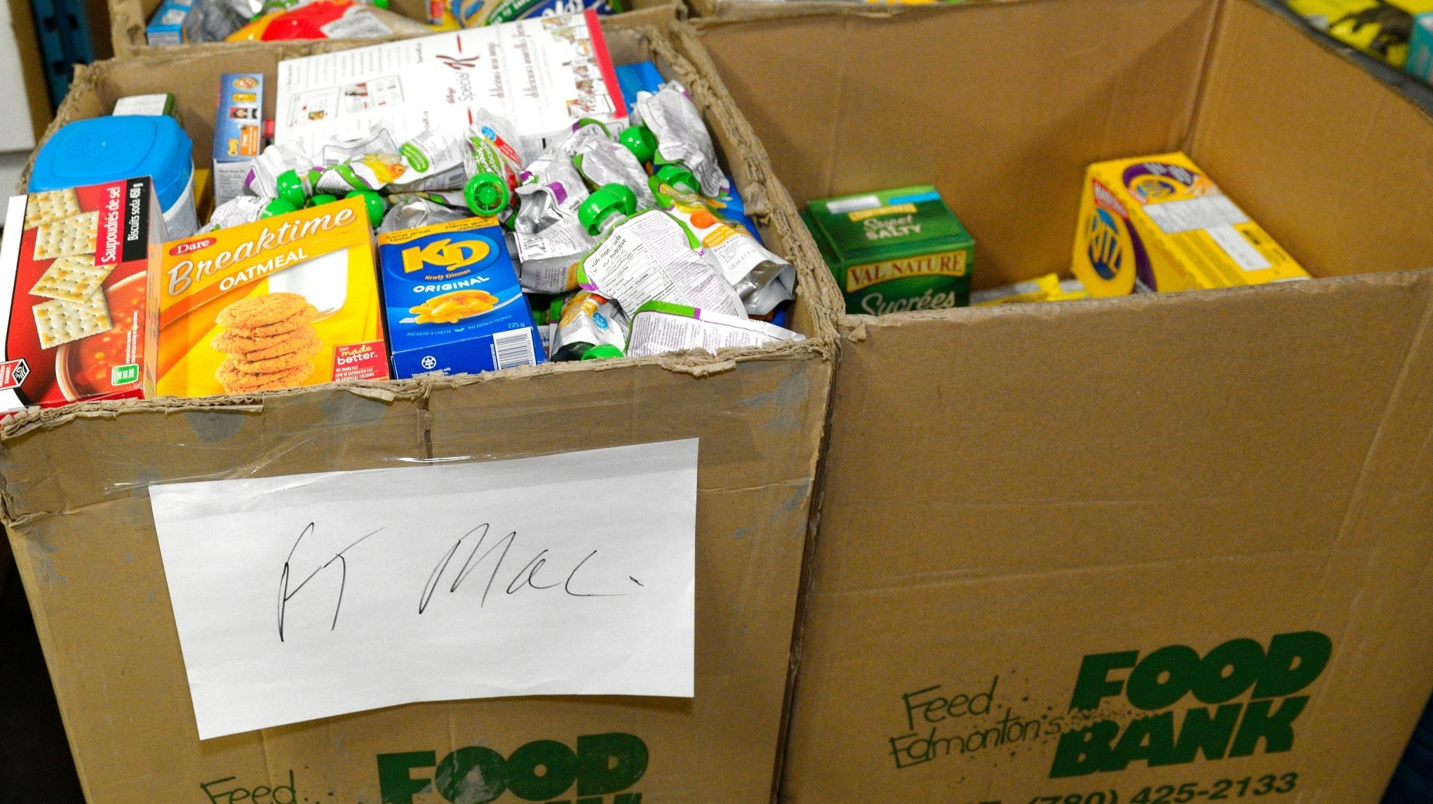 Several boxes from the food bank, filled with food, with a sign that reads 'Ft McMurray'