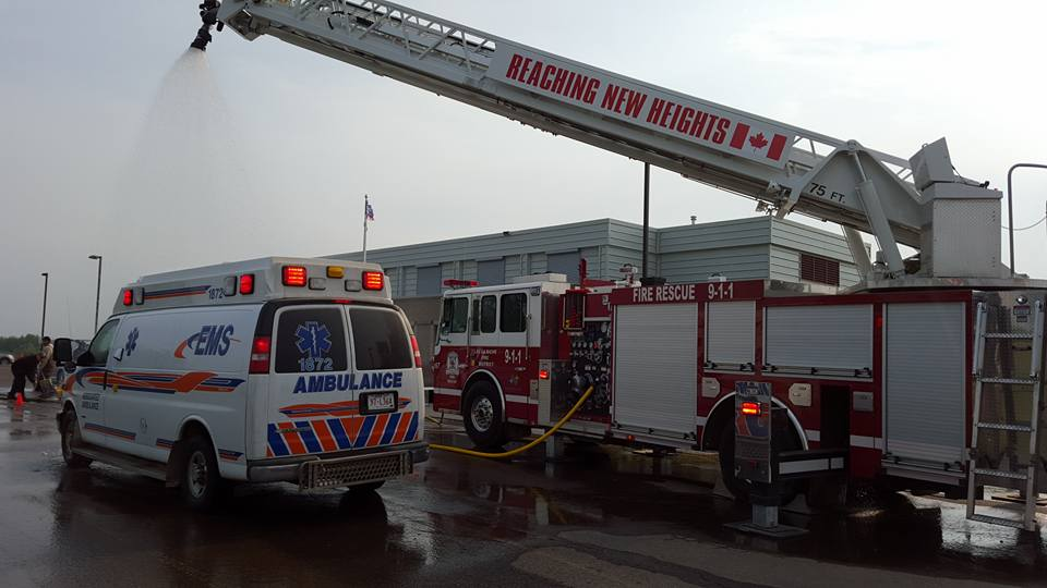 A fire truck with a spray nozzle on the crane is washing down an ambulance in a parking lot.