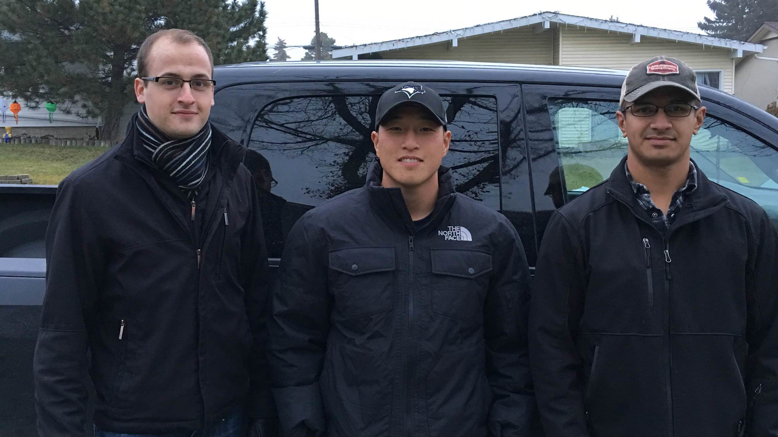 Three men standing in front of a black truck.