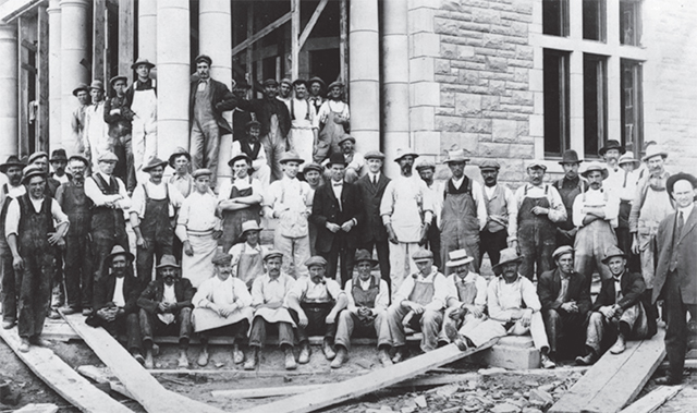 An archival group photo of a construction crew standing in front of the Government House entrance.