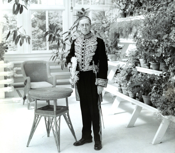 The Lieutenant Governor, standing by a table in a conservatory in full regalia.