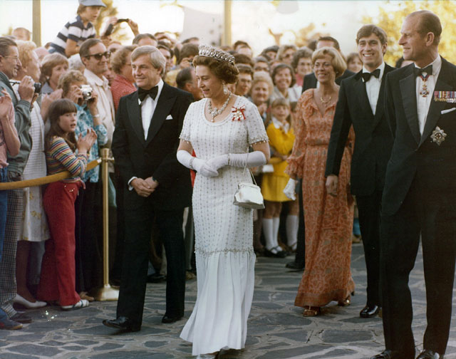 An archival photo of Queen Elizabeth the Second walking, with a crowd of people watching.
