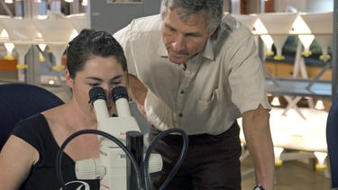 A researcher looking at a slide under a microscrope while an instructor observes.